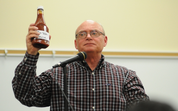 Brentwood Booster Club President Bill Koster auctions a bottle of Christina Pudlowski's homemade barbecue sauce.
