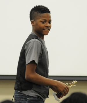 Eighth-grader Courtland Hill smiles after receiving the Outstanding Offensive Player Award. He plays quarterback.