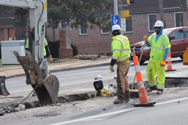 Missouri American Water workers use a back hoe to dig a trench to reach the old water main.