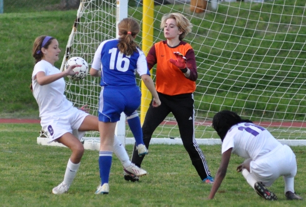 Natalie Featherston tries to get the ball away from No. 16 of Crossroads as goalkeeper Audrey Brown stands guard.