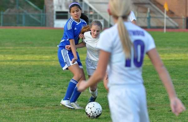 Julianna Nikodym tries to break loose from a Crossroads player to pass to Kate Gilmore.