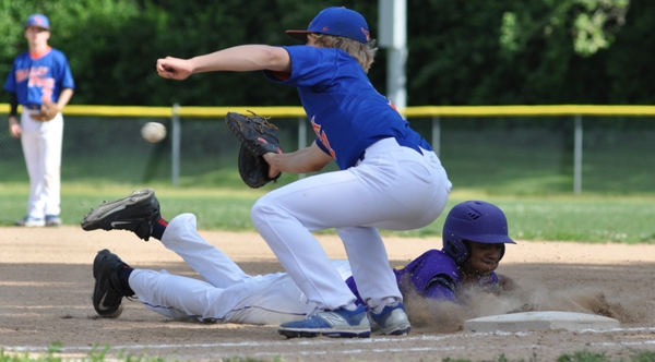 Charles Jones dives safely back to first base in the third inning.