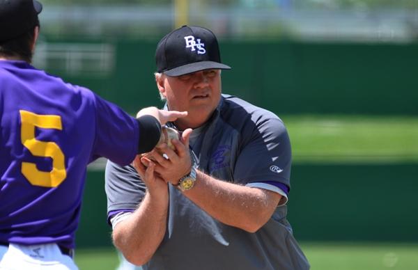 Brentwood assistant coach John Sappington rounds up baseballs after pregame warmups.