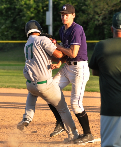 Sam Tilton attempts to tag out a runner at first base who had taken a big lead.