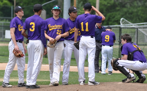 Brentwood players wait near the pitcher's mound while Mike Imergoot questions the umpire about the call at first base.