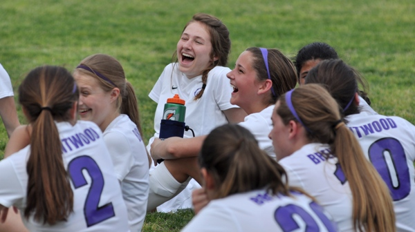 Junior Tara Lochmoeller enjoys a joke with Natalie Featherston during halftime of a soccer game in 2014. Though a back injury kept Lochmoeller from playing for the entire season, she attended the games and supported her teammates.