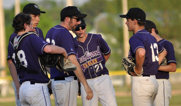 Junior varsity coach Zach Sias and Brentwood infielders meet with Luke Tilton on the pitcher's mound.