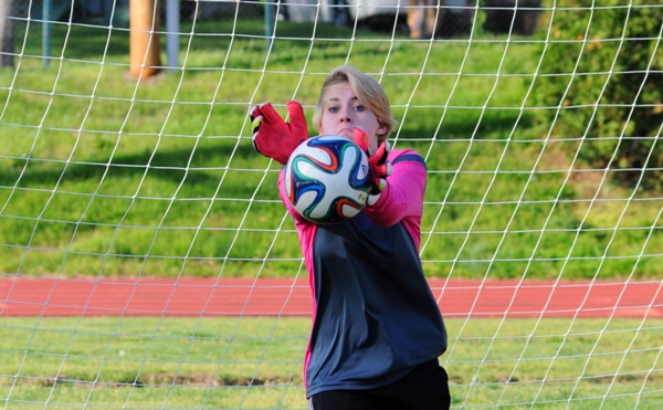 Brentwood goalkeeper Audrey Brown stops a shot from assistant coach Rob Doebber in warmups before the Hancock game on April 23.