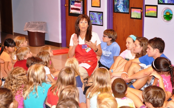 """Tommy Heinemann's mother, Janet, speaks to students at an art camp at Mount Calvary Lutheran Church in 2011. She encouraged him to hold a soccer camp when he was 11. """"We have a big family in the St. Louis area and my son is used to being around kids,"""" she said. """"He really is good with kids."""" (Photo by Steve Bowman)"""