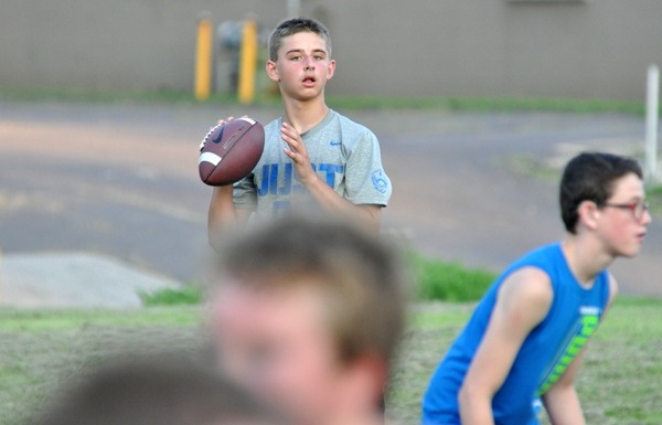 Eighth grader Nathan Butler looks for a receiver. He was quarterback of the seventh graders last year.