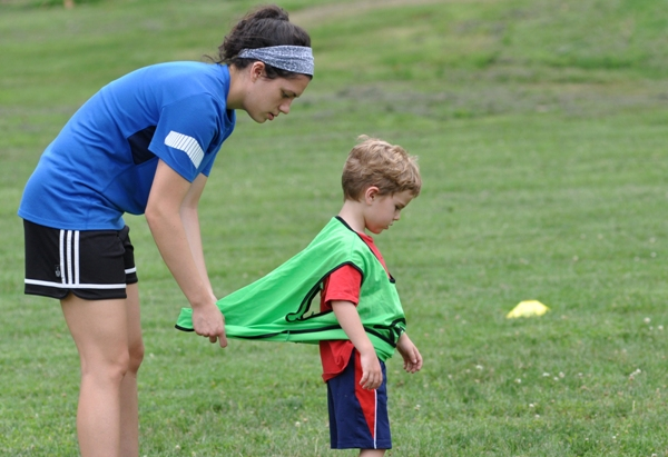 Karlee Heinemann, Tommy's sister, adjusts a scrimmage vest to fit a youngster at the Heinemann Soccer Camp on June 23 at Norm West Field in Brentwood. She played soccer for Rockhurst University and is about to start her senior year majoring in business administration. (Photo by Steve Bowman)