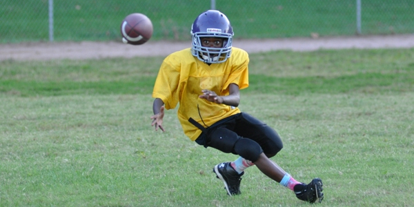 Seventh grader Chris Robinson eyes a pass from Michael Jones in practice Sept. 22 at Brentwood Park. (All photos by Steve Bowman)