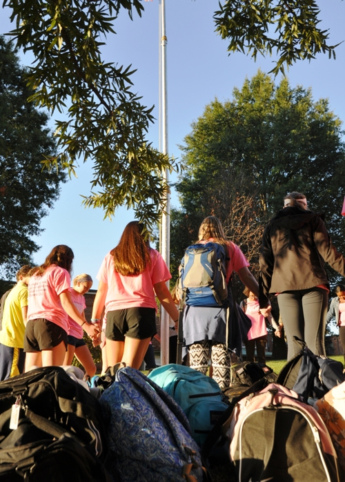 Students set their backpacks aside and pray before their morning classes.