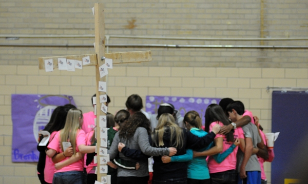 Students huddle to pray behind a cross covered with prayer requests at Fields of Faith, an event hosted by the Fellowship of Christian Athletes group at Brentwood High School on Wednesday night. (All photos by Steve Bowman)