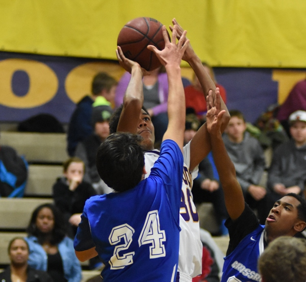 Nigel Bracey shoots over a cluster of Crossroads players.