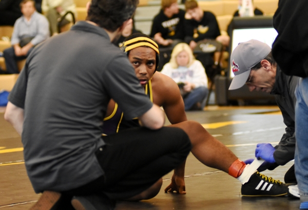 Gary Silerio listens to Mic Boshans during a timeout to have his ankle taped during a match with Matt Green of MRH at St. John Vianney.