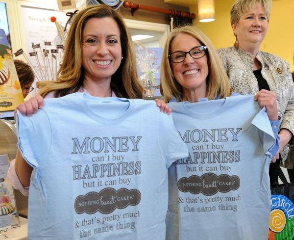 Janelle Amell (left) and Jenni Schroeder show off the t-shirts they received at the ribbon-cutting.