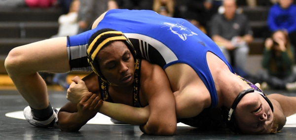 Gary Silerio tries to pin Dillion Liefer of Lutheran St. Charles. Silerio won with a major decision.