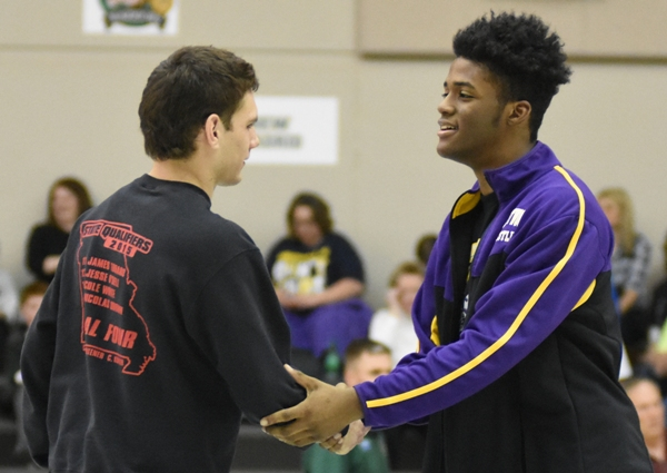 """Deshaun Johnson (right) shakes hands with Cole White of Herculaneum before their match in the finals of the district tournament. Before the third- and first-place matches a ceremony is held in which each wrestler shakes hands with his competitor. Johnson said of White, """"He's a good friend of mine so I don't really have much animosity toward him."""" Whit won the match for third place but both qualified for state."""