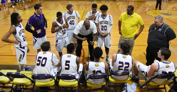 Assistant coach Dennis Buckley talks during a timeout against Trinity. Head coach Kevin Kullum (yellow shirt) and Dan assistant Dan Williams (far right) look on.