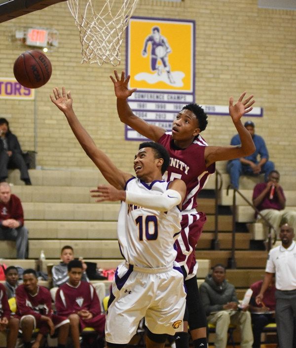 Charles Jones tries to shoot a layup while pursued by two Trinity players.