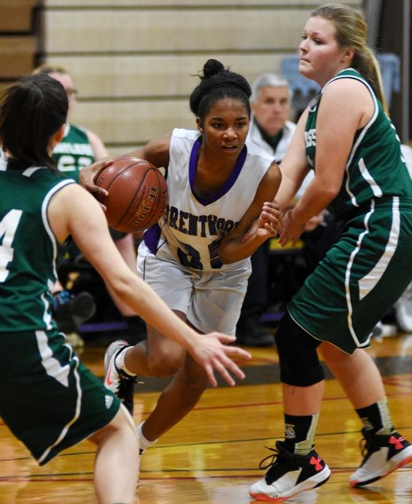 Nija Price drives to the hoop between two Bayless defenders.