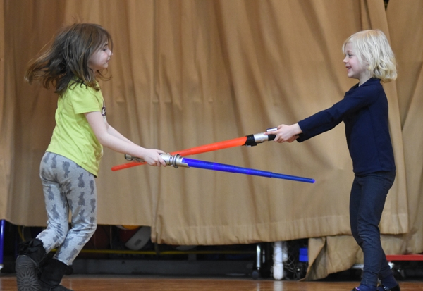 Second grader Carly Selig (left) and kindergartener Claire Hansen spar with light sabers in dress rehearsal. At the talent show they performed with the lights off and only their lit swords showing. They were accompanied on piano by Brady Hansen, who played a Stars Wars medley.