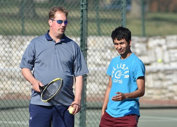 Head coach Jeff Heinrich speaks with junior Marcos Sanhez
