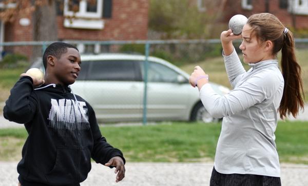 Talking shot put technique are Tayveon Brown and Sophia Rivera.
