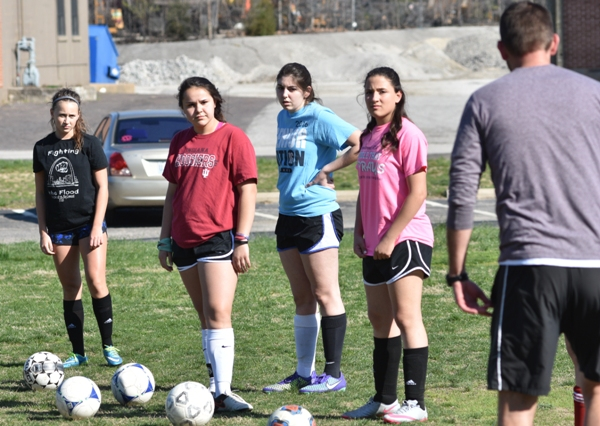 Cory Grage explains a practice drill to (from left) Elle Curran, Maggie Callihan, senior Megan Shipley and freshman Rachel Walthall.