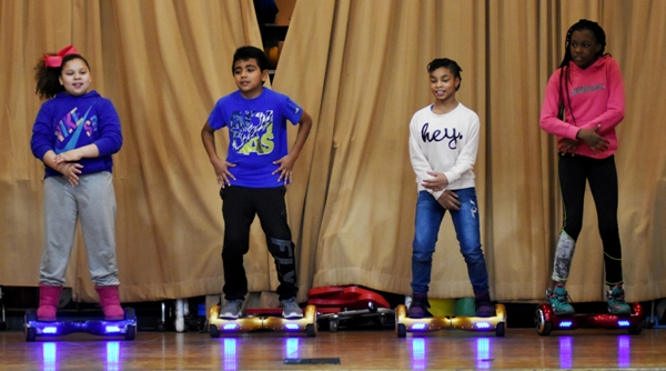 """In dress rehearsal (above) and on performance night (below) is the """"hover board squad,"""" made up of fifth graders (from left) Jamia Welch, Eric Rojas, McKenzie Hamilton and Kennadie Miller."""