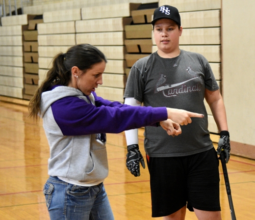 Assistant coach Natalee Rujawitz instructs Daniel Doebber on hitting.