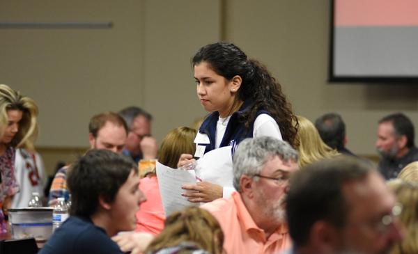 Senior Sarah Thomas gathers answer sheets from the trivia teams.