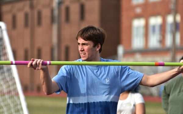 Jacob Menne steadies the high jump crossbar.