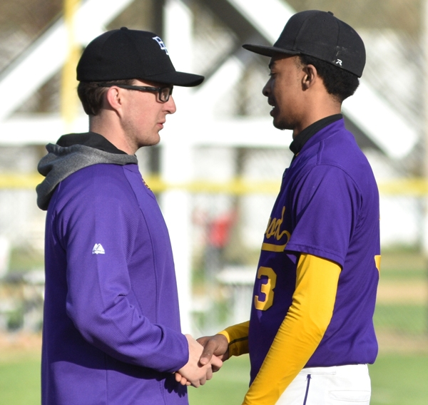 Assistant coach Elliott Sterett (left) encourages Butters Jones after Jones pitched the final out of the sixth inning.