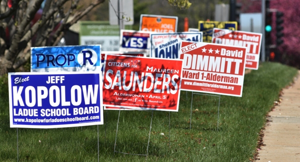 Outside McKnight Crossing Church are signs for Maureen Saunders, David Dimmitt and others.