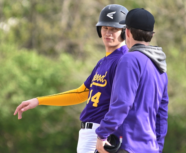 Sam Tilton talks with first-base coach Elliott Sterett in the DuBourg game.
