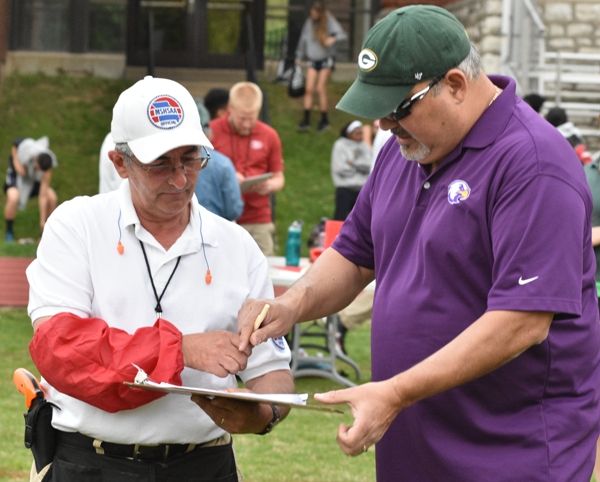 MSHSAA official Jon Doe (left) signs a sheet held by Sophia's father, Edwin Rivera, verifying that she had thrown 180 feet 4 inches.