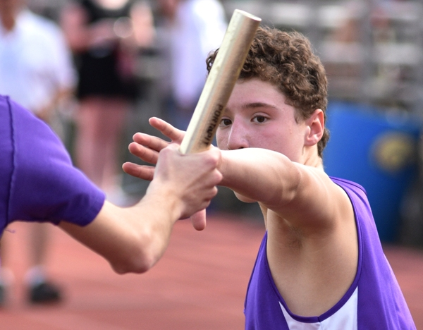 John Waltham takes the baton from Jackson Neely in the 3,200 relay.
