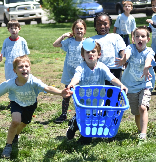 Students try to catch a water balloon in a laundry basket.