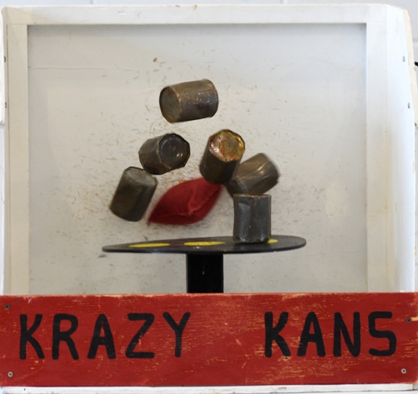 A student throws knocks over cans with a bean bag in the Krazy Kans game.