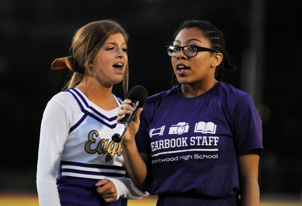 Evan Adams (right) sings the National Anthem in harmony with Sydney Moreno before a football game in 2015.