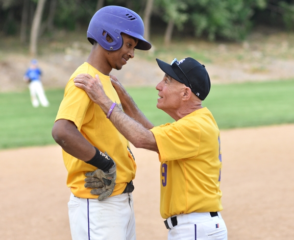 """Brentwood coach Mike Imergoot speaks with Charles """"Butters"""" Jones at third base in the eighth inning."""