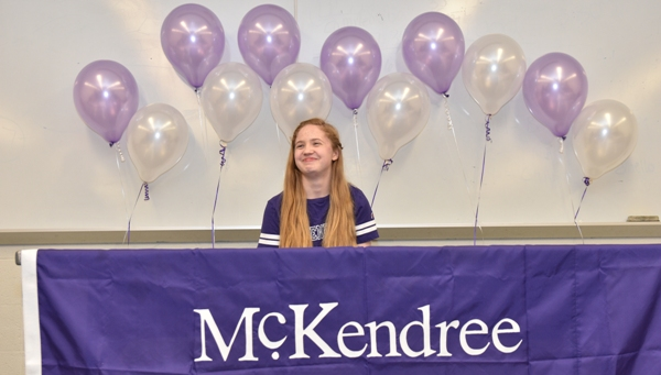 Victoria Aunger smiles while BHS athletic director Steve Ayotte tells a roomful of family members, students and teachers about her on May 11 in the school's lecture room. Soon after Ayotte's comments, she signed a letter of intent to join the McKendree University color guard this fall. (Photo by Steve Bowman)