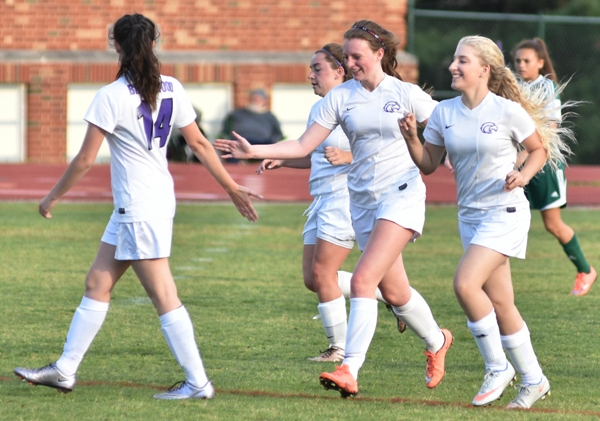 Maddie Dorenbusch (middle) gets a hand slap from Amanda Ingersoll (left) and a smile from Rebecca Walthall after scoring to make it 4-0 against Bayless.