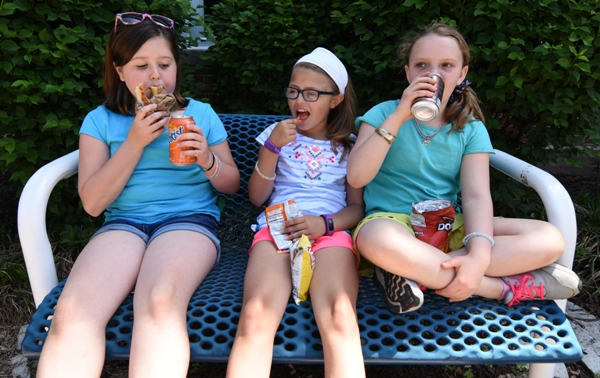 Enjoying snacks outside are friends (from left) Amelia Favazza, Ava Amad and Amelia Spencer.