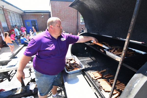 Tom Magee (above) cooks the hot dogs and brats and his wife Lisa Magee (below) takes them to the serving table.