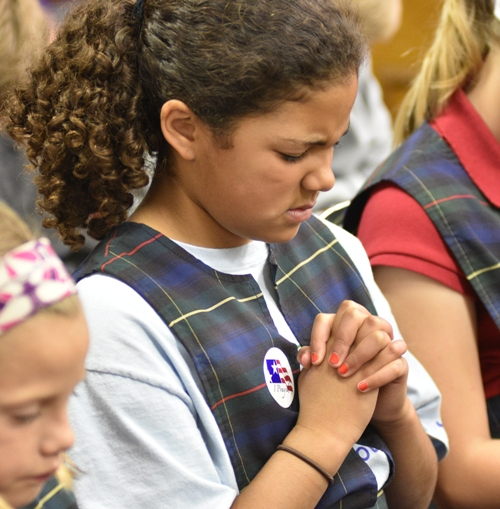 A student folds her hands in prayer.