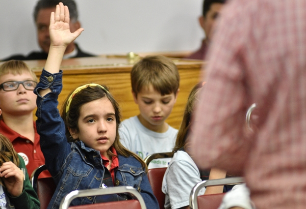 A student from St. Mary Magdalen Catholic School raises her hand to share a prayer request.
