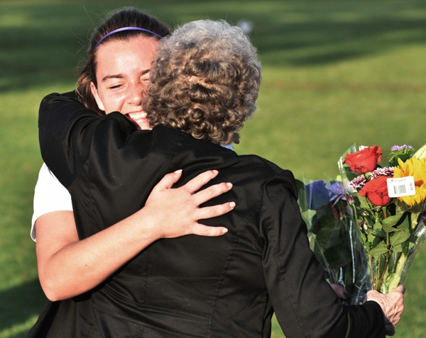 Abby Harper hugs her grandmother, Betty McDonald, during the senior night program during halftime of the Bayless game.